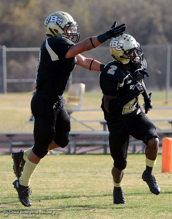 . Butte College\'s #7 Ryan Holland (left) celebrates #2 Deonte Flemings (right) on intercepting a pass against Fullerton College in the first quarter of their CCCAA football state championship final at Butte\'s Cowan Stadium Saturday, December 14, 2013 in Butte Valley, Calif. (Jason Halley/Chico Enterprise-Record)