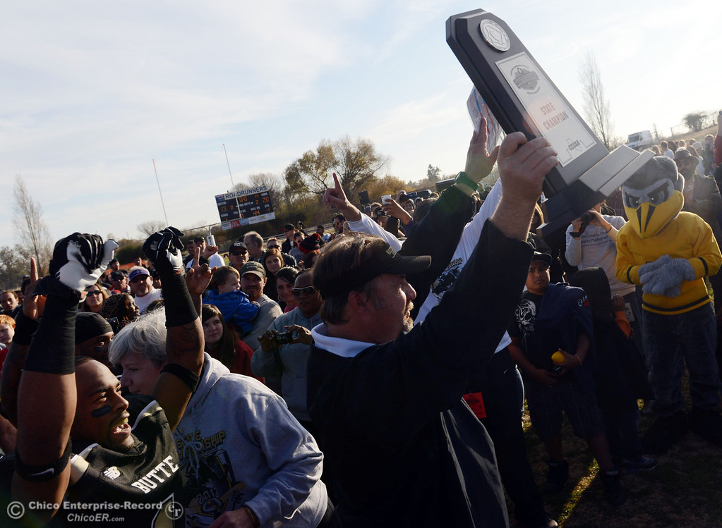 . Butte College head coach Jeff Jordan holds up the championship trophy in their win against Fullerton College at the end of the fourth quarter of their CCCAA football state championship final at Butte\'s Cowan Stadium Saturday, December 14, 2013 in Butte Valley, Calif. (Jason Halley/Chico Enterprise-Record)