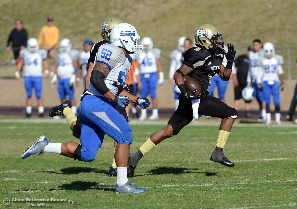 . Butte College\'s #1 Wes McCoy (right) returns a kickoff for a touchdown against San Mateo College in the third quarter of their football game at Butte\'s Cowan Stadium Saturday, November 2, 2013 in Oroville, Calif.  (Jason Halley/Chico Enterprise-Record)