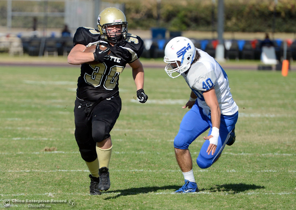 . Butte College\'s #30 Eric DeLucchi (left) runs the ball against College of San Mateo\'s #40 Jake Kearney (right) in the second quarter of their football game at Butte\'s Cowan Stadium Saturday, November 2, 2013 in Oroville, Calif.  (Jason Halley/Chico Enterprise-Record)