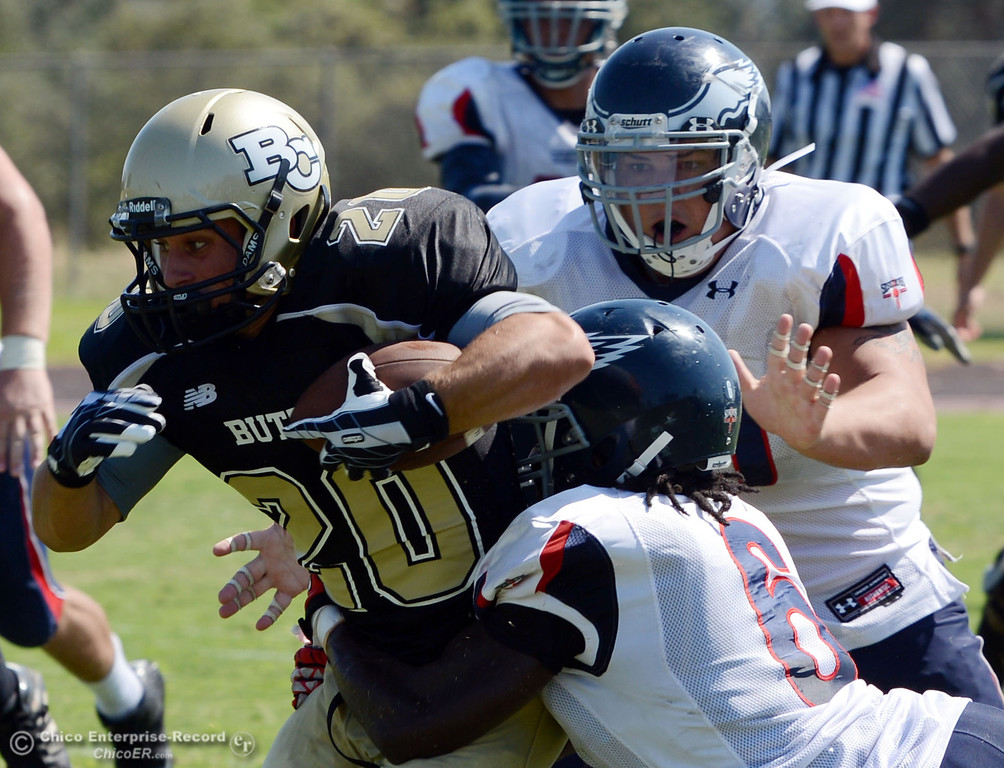. Butte College\'s #20 Armand Bokitch (left) is tackled against College of the Siskiyous\' #6 Michael Everett (bottom) and #70 Nick Hendesron (right) in the second quarter of their football game at Butte\'s Cowan Stadium on Saturday, September 14, 2013, in Oroville, Calif. (Jason Halley/Chico Enterprise-Record)