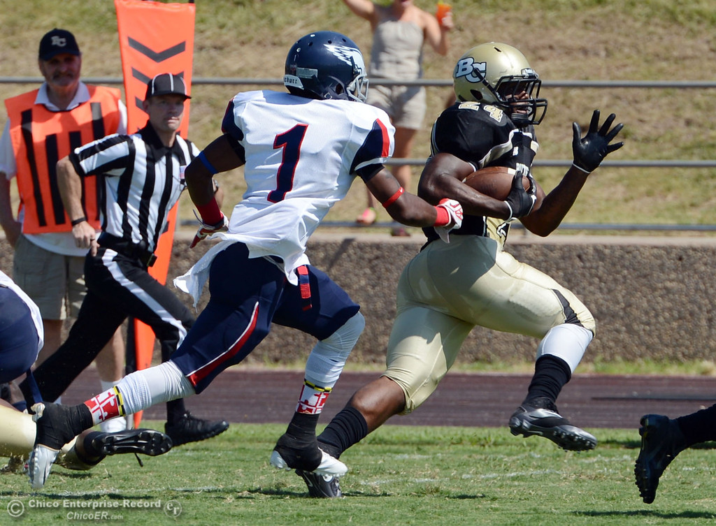 . Butte College\'s #24 Kendall Williams (center) rushes against College of the Siskiyous\' #1John Holland (left) in the first quarter of their football game at Butte\'s Cowan Stadium on Saturday, September 14, 2013, in Oroville, Calif. (Jason Halley/Chico Enterprise-Record)