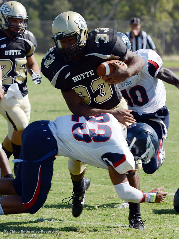 . Butte College\'s #33 Jariah Booker (top) is tackled against College of the Siskiyous\' #23 Zach Floyd (bottom) on a recovered fumble in the third quarter of their football game at Butte\'s Cowan Stadium on Saturday, September 14, 2013, in Oroville, Calif. (Jason Halley/Chico Enterprise-Record)