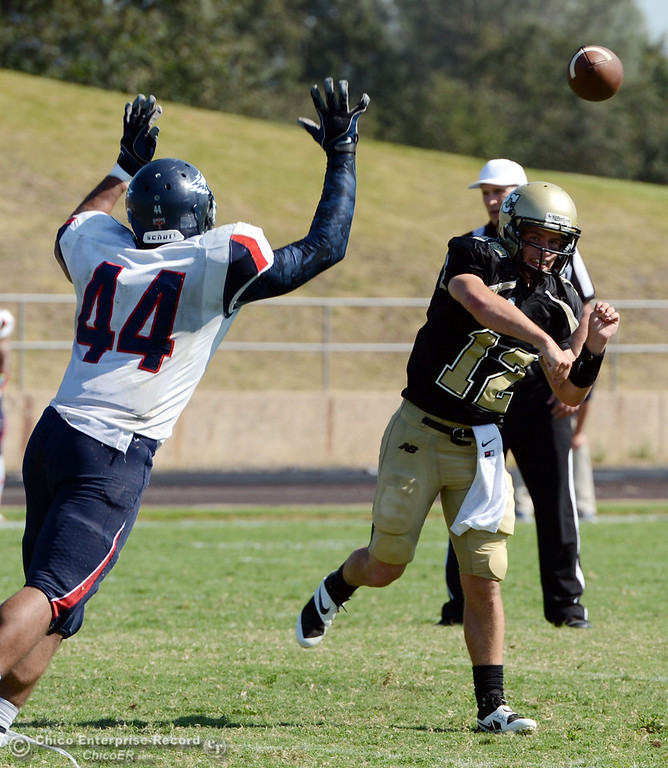 . Butte College\'s #12 Thomas Stuart (right) passes against College of the Siskiyous\' #44 Justin Merriweather (left) in the third quarter of their football game at Butte\'s Cowan Stadium on Saturday, September 14, 2013, in Oroville, Calif. (Jason Halley/Chico Enterprise-Record)