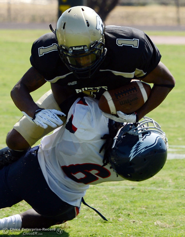 . Butte College\'s #1 Wes McCoy (top) is tackled against College of the Siskiyous\' #6 Michael Everett (bottom) in the second quarter of their football game at Butte\'s Cowan Stadium on Saturday, September 14, 2013, in Oroville, Calif. (Jason Halley/Chico Enterprise-Record)