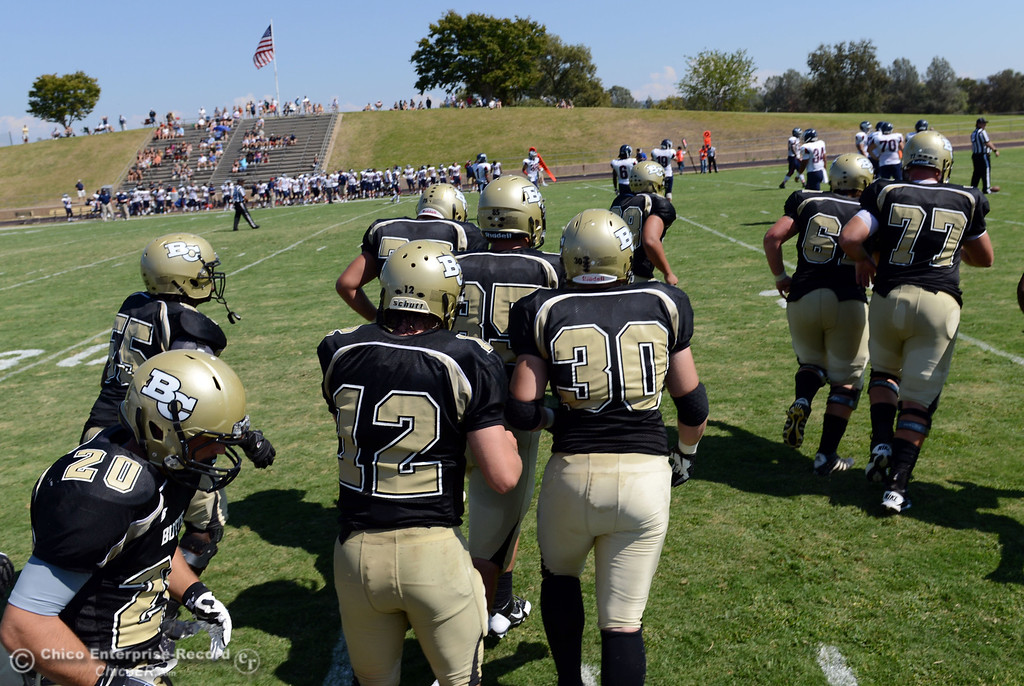 . Butte College\'s #20 Armand Bokitch (left) and others take the field against College of the Siskiyous in the second quarter of their football game at Butte\'s Cowan Stadium on Saturday, September 14, 2013, in Oroville, Calif. (Jason Halley/Chico Enterprise-Record)