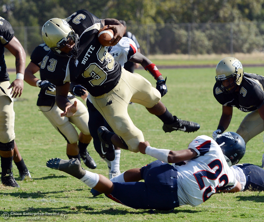 . Butte College\'s #33 Jariah Booker (center) is tackled against College of the Siskiyous\' #23 Zach Floyd (bottom) after Booker picked up a fumble in the third quarter of their football game at Butte\'s Cowan Stadium on Saturday, September 14, 2013, in Oroville, Calif. (Jason Halley/Chico Enterprise-Record)