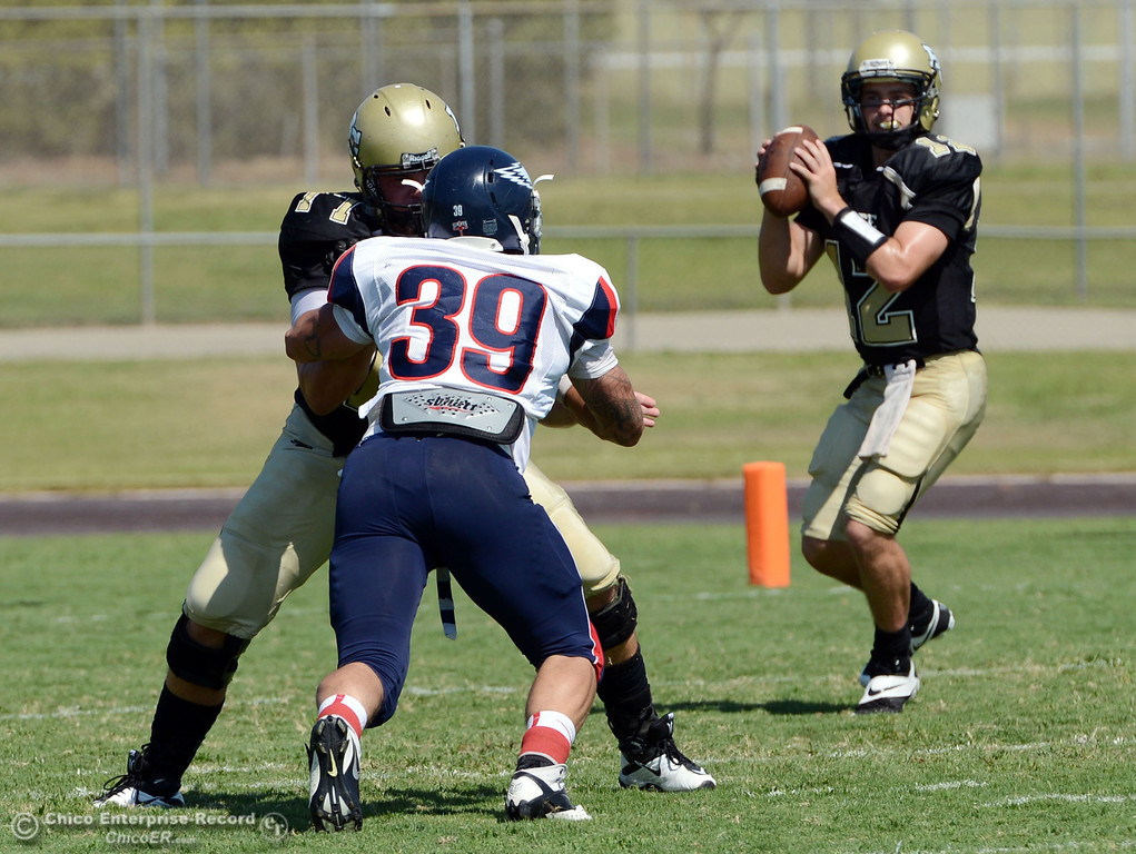 . Butte College\'s #12 Thomas Stuart drops back to pass as #77 Scott Batchelder (left) blocks against College of the Siskiyous\'s  #39 Derek Hurschman (center) in the first quarter of their football game at Butte\'s Cowan Stadium on Saturday, September 14, 2013, in Oroville, Calif. (Jason Halley/Chico Enterprise-Record)