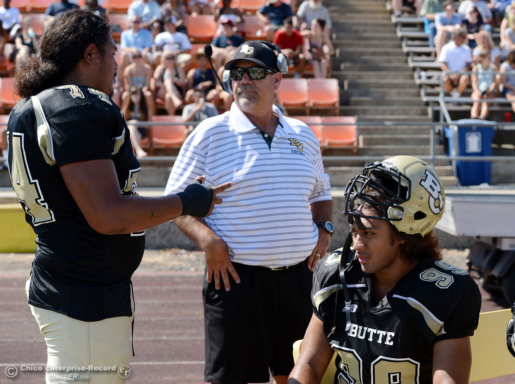 . Butte College #74 Christopher Siliga (left) talks to Willie Thomas (center) next to #99 Leopeni Siania (right) against College of the Siskiyous in the second quarter of their football game at Butte\'s Cowan Stadium on Saturday, September 14, 2013, in Oroville, Calif. (Jason Halley/Chico Enterprise-Record)