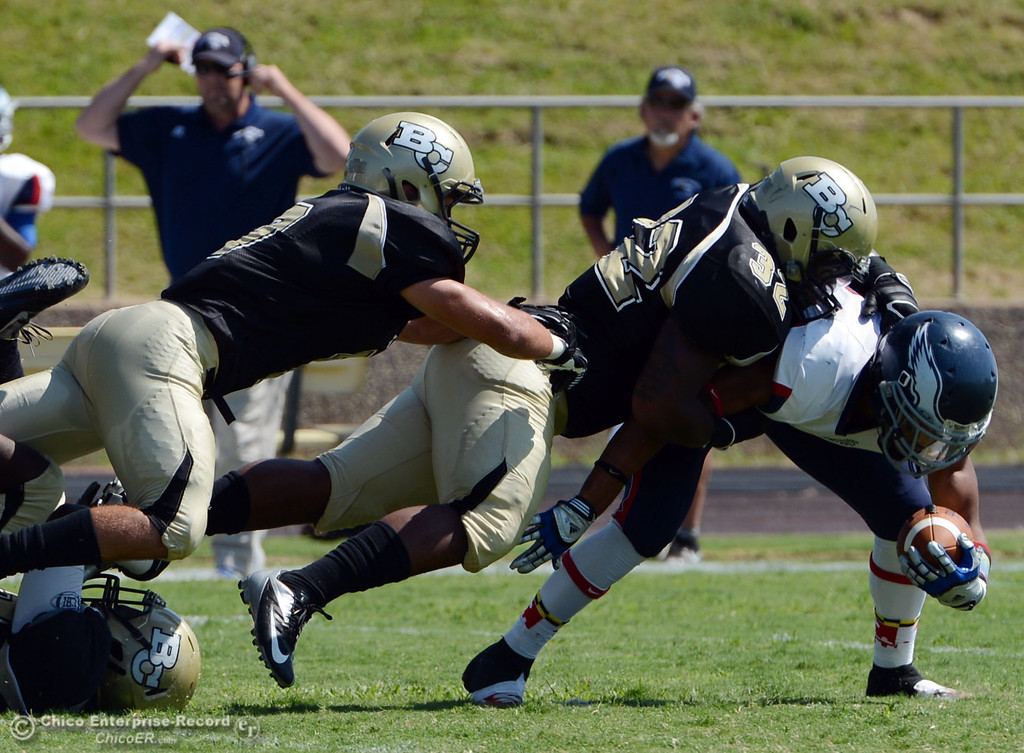 . Butte College\'s #7 Ryan Holland (left) and #32 Brian Anderson (center) tackle against College of the Siskiyous\' #4 Aaron Williams (right) in the first quarter of their football game at Butte\'s Cowan Stadium on Saturday, September 14, 2013, in Oroville, Calif. (Jason Halley/Chico Enterprise-Record)