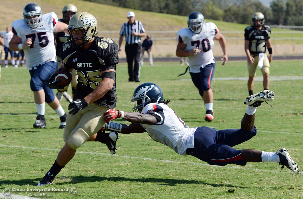 . Butte College\'s #85 Richard Murphy (center) rushes against College of the Siskiyous\' #6 Michael Everett (right) in the third quarter of their football game at Butte\'s Cowan Stadium on Saturday, September 14, 2013, in Oroville, Calif. (Jason Halley/Chico Enterprise-Record)
