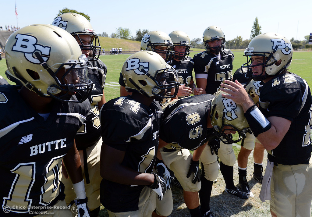 . Butte College\'s #12 Thomas Stuart (right) talks to the offensive line against College of the Siskiyous in the first quarter of their football game at Butte\'s Cowan Stadium on Saturday, September 14, 2013, in Oroville, Calif. (Jason Halley/Chico Enterprise-Record)