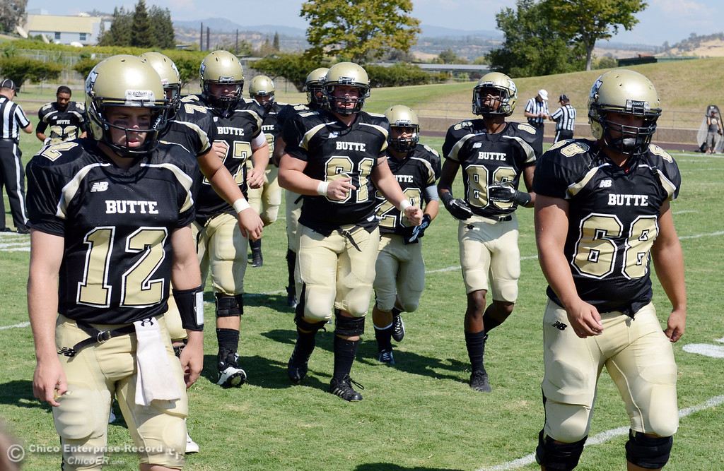 . Butte College\'s #12 Thomas Stuart (left) and #68 Eli Thom (right) come off the field against College of the Siskiyous in the second quarter of their football game at Butte\'s Cowan Stadium on Saturday, September 14, 2013, in Oroville, Calif. (Jason Halley/Chico Enterprise-Record)