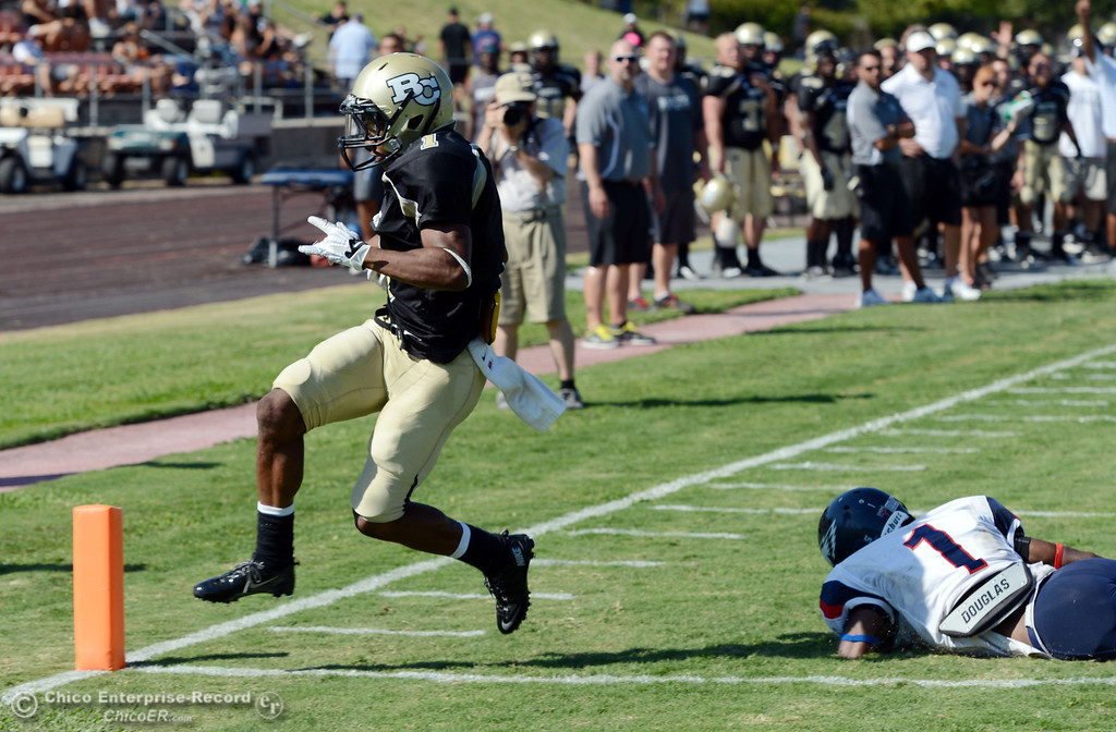 . Butte College\'s #1 Wes McCoy (left) scores a touchdown against College of the Siskiyous\' #1 John Holland (right) in the fourth quarter of their football game at Butte\'s Cowan Stadium on Saturday, September 14, 2013, in Oroville, Calif. (Jason Halley/Chico Enterprise-Record)