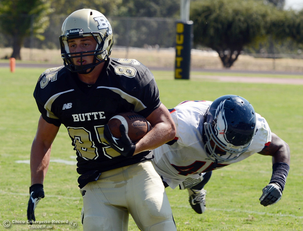 . Butte College\'s #85 Ricahrd Murphy (left) rushes against College of the Siskiyous\' #45 Kerry Stabler (right) in the second quarter of their football game at Butte\'s Cowan Stadium on Saturday, September 14, 2013, in Oroville, Calif. (Jason Halley/Chico Enterprise-Record)