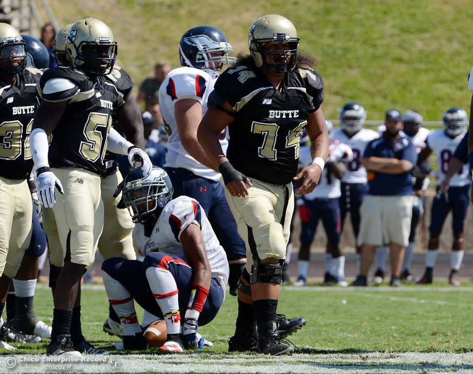 . Butte College\'s #74 Christopher Siliga (center) against College of the Siskiyous in the first quarter of their football game at Butte\'s Cowan Stadium on Saturday, September 14, 2013, in Oroville, Calif. (Jason Halley/Chico Enterprise-Record)
