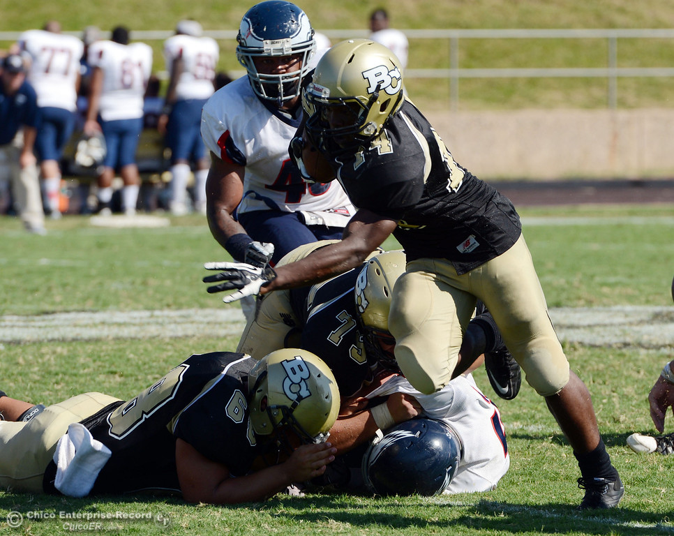 . Butte College\'s #14Robert Frazier (center) rushes against College of the Siskiyous in the third quarter of their football game at Butte\'s Cowan Stadium on Saturday, September 14, 2013, in Oroville, Calif. (Jason Halley/Chico Enterprise-Record)