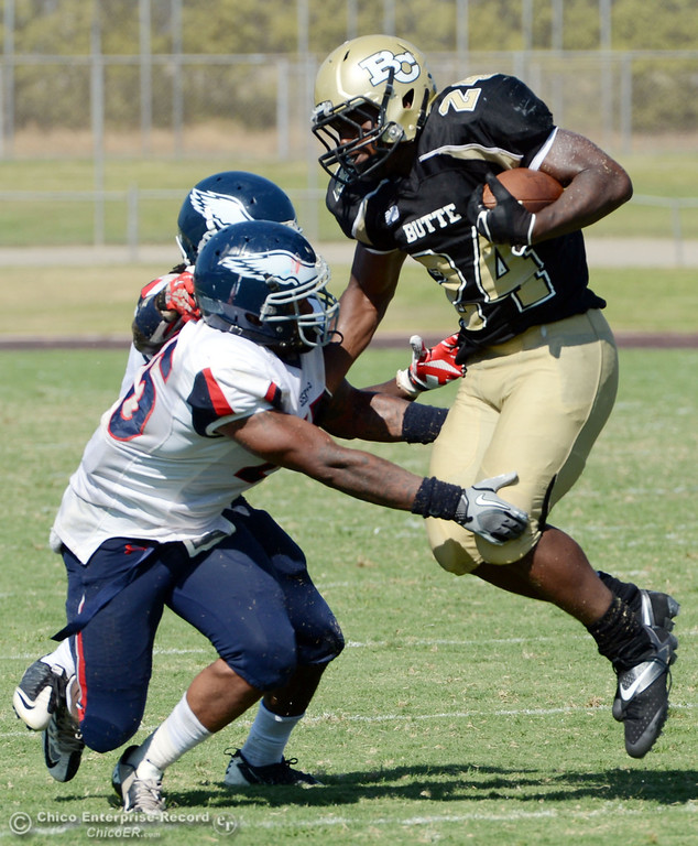 . Butte College\'s #24 Kendall Williams (right) is tackled against College of the Siskiyous\' #45 Kerry Stabler (left) in the third quarter of their football game at Butte\'s Cowan Stadium on Saturday, September 14, 2013, in Oroville, Calif. (Jason Halley/Chico Enterprise-Record)