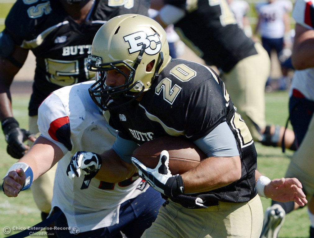 . Butte College\'s #20 Armand Bokitch (right) is tackled against College of the Siskiyous\' #19 Alex Henderson (left) in the third quarter of their football game at Butte\'s Cowan Stadium on Saturday, September 14, 2013, in Oroville, Calif. (Jason Halley/Chico Enterprise-Record)
