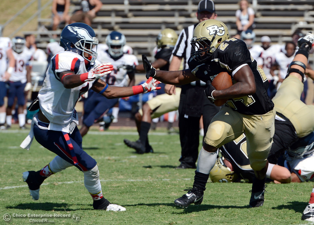 . Butte College\'s #24 Kendall Williams (right) rushes against College of the Siskiyous\' #1 John Holland (left) in the third quarter of their football game at Butte\'s Cowan Stadium on Saturday, September 14, 2013, in Oroville, Calif. (Jason Halley/Chico Enterprise-Record)