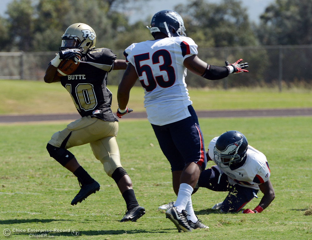 . Butte College\'s #10 CJ Grice (left) rushes against College of the Siskiyous\' #53 Andre Hughes (center) and #29 Yves Nguessan (right) in the second quarter of their football game at Butte\'s Cowan Stadium on Saturday, September 14, 2013, in Oroville, Calif. (Jason Halley/Chico Enterprise-Record)