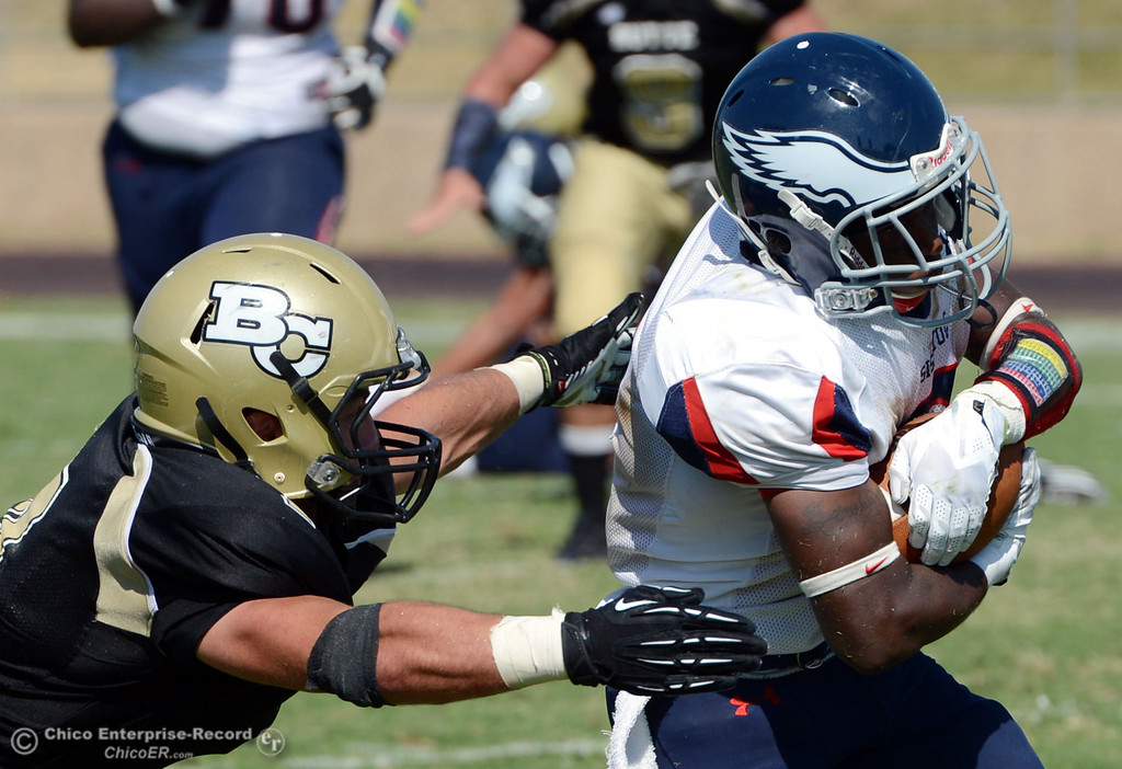 . Butte College\'s #7 Ryan Holland (left) tackles against College of the Siskiyous\' #2 Demetrius Brown (right) in the third quarter of their football game at Butte\'s Cowan Stadium on Saturday, September 14, 2013, in Oroville, Calif. (Jason Halley/Chico Enterprise-Record)