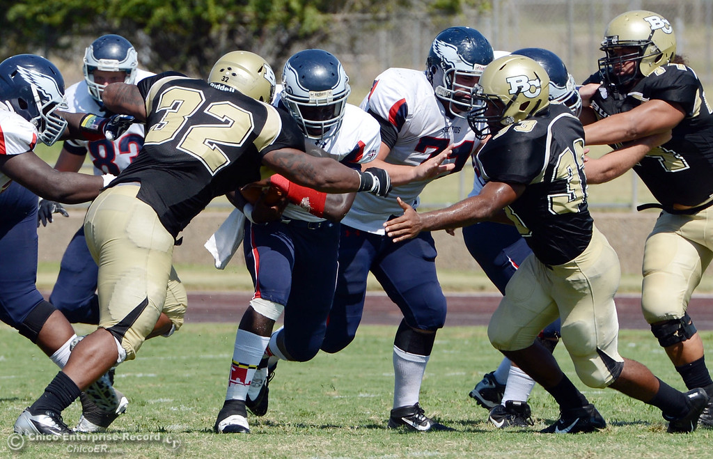 . Butte College\'s #32 Brian Anderson (left) and #33 Jariah Booker (right) tackle against College of the Siskiyous\' #7 Warren Johnson (center) in the second quarter of their football game at Butte\'s Cowan Stadium on Saturday, September 14, 2013, in Oroville, Calif. (Jason Halley/Chico Enterprise-Record)