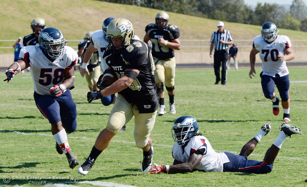 . Butte College\'s #85 Richard Murphy (center) rushes against College of the Siskiyous\' #58 Tyrese Lyons (left) and #6 Michael Everett (right) in the third quarter of their football game at Butte\'s Cowan Stadium on Saturday, September 14, 2013, in Oroville, Calif. (Jason Halley/Chico Enterprise-Record)
