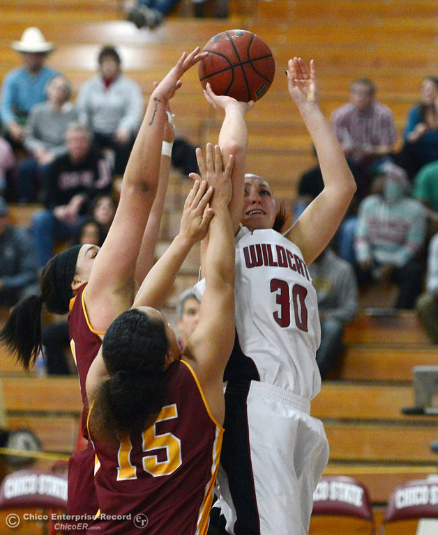 . Chico State\'s #30 McKenzie Dalthorp (right) goes up for a shot against Cal State Dominguez Hills\' #15 Monay Lee (left) and #3 Tayler Champion (back) in the second half of their women\'s basketball game at CSUC Acker Gym Friday, January 10, 2014 in Chico, Calif.  (Jason Halley/Chico Enterprise-Record)