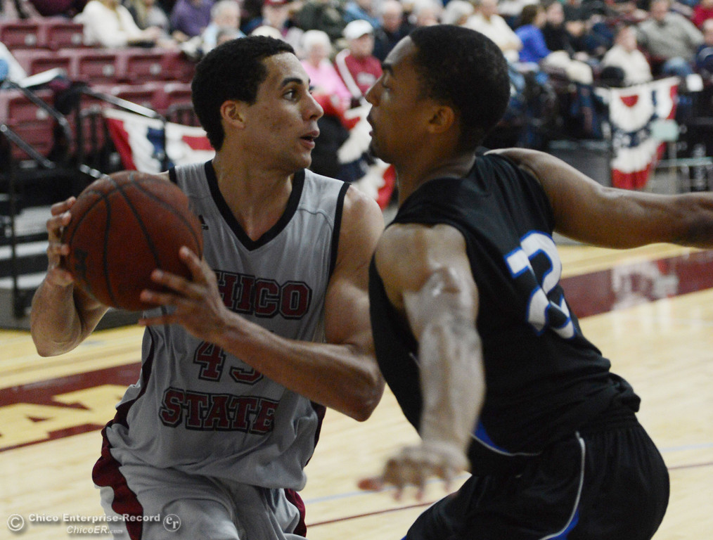 . Chico State\'s #45 Jordan Semple (left) dribbles against Cal State San Bernardino\'s #22 Joshua Gouch (right) in the second half of their men\'s basketball game at CSUC Acker Gym Saturday, February 8, 2014 in Chico, Calif.  (Jason Halley/Chico Enterprise-Record)