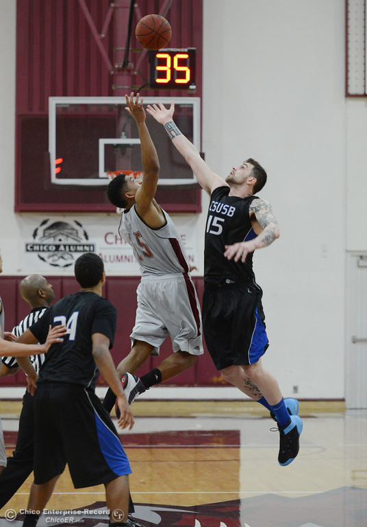 . Chico State\'s #15 Amir Carraway (left) goes up for a jump ball against Cal State San Bernardino\'s #15 Andrew Young (right) in overtime of their men\'s basketball game at CSUC Acker Gym Saturday, February 8, 2014 in Chico, Calif.  (Jason Halley/Chico Enterprise-Record)