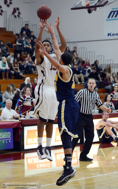 . Chico State\'s #15 Amir Carraway (left) takes a shot against UC San Diego\'s #23 Hunter Walker (right) in the first half of their men\'s basketball game at CSUC Acker Gym Friday, February 7, 2014 in Chico, Calif.  (Jason Halley/Chico Enterprise-Record)