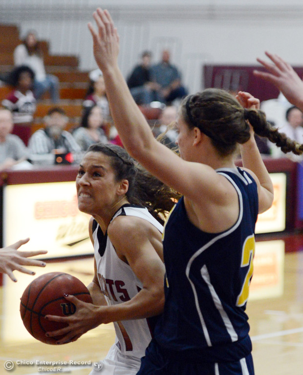 . Chico State\'s #21 Courtney Hamilton (left) drives to the basket against UC San Diego\'s #21 Megan Perry (right) in the first half of their women\'s basketball game at CSUC Acker Gym Friday, February 7, 2014 in Chico, Calif.  (Jason Halley/Chico Enterprise-Record)