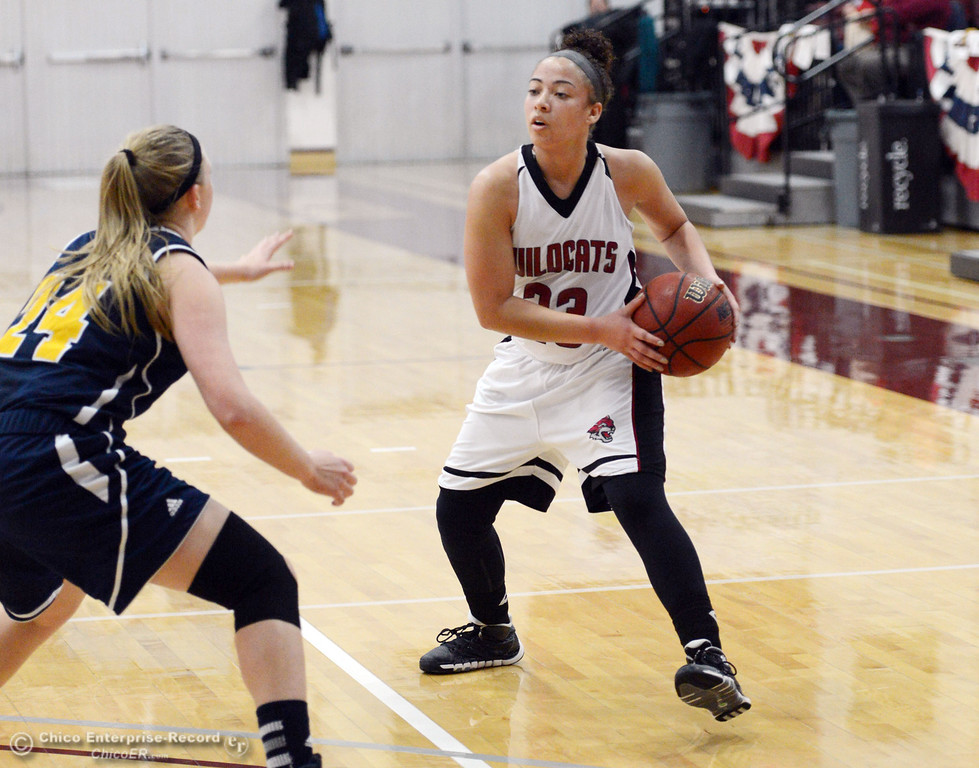 . Chico State\'s #23 Jazmine Miller (right) looks to pass against UC San Diego\'s #24 Haley Anderson (left) in the first half of their women\'s basketball game at CSUC Acker Gym Friday, February 7, 2014 in Chico, Calif.  (Jason Halley/Chico Enterprise-Record)