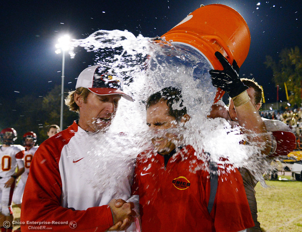 . Chico High\'s #58 Malik Hopkins (right) pours a bucket of water of coaches Kevin Wisdom (left) and Jason Alvistur (center) against Pleasant Valley High in the fourth quarter of their Almond Bowl football game at CSUC University Stadium Friday, November 1, 2013 in Chico, Calif.  (Jason Halley/Chico Enterprise-Record)