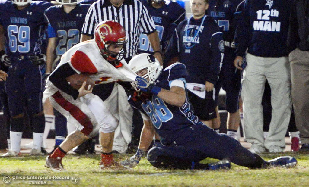 . Chico High\'s #15 Miles Fishback (left) is tackled against Pleasant Valley High\'s #88 Zack Suttles (right) in the fourth quarter of their Almond Bowl football game at CSUC University Stadium Friday, November 1, 2013 in Chico, Calif.  (Jason Halley/Chico Enterprise-Record)