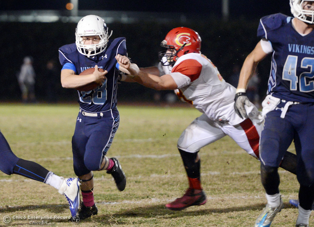 . Pleasant Valley High\'s #28 Dylan Batie (left) rushes for a touchdown against Chico High\'s #58 Malik Hopkins (right) in the first quarter of their Almond Bowl football game at CSUC University Stadium Friday, November 1, 2013 in Chico, Calif.  (Jason Halley/Chico Enterprise-Record)