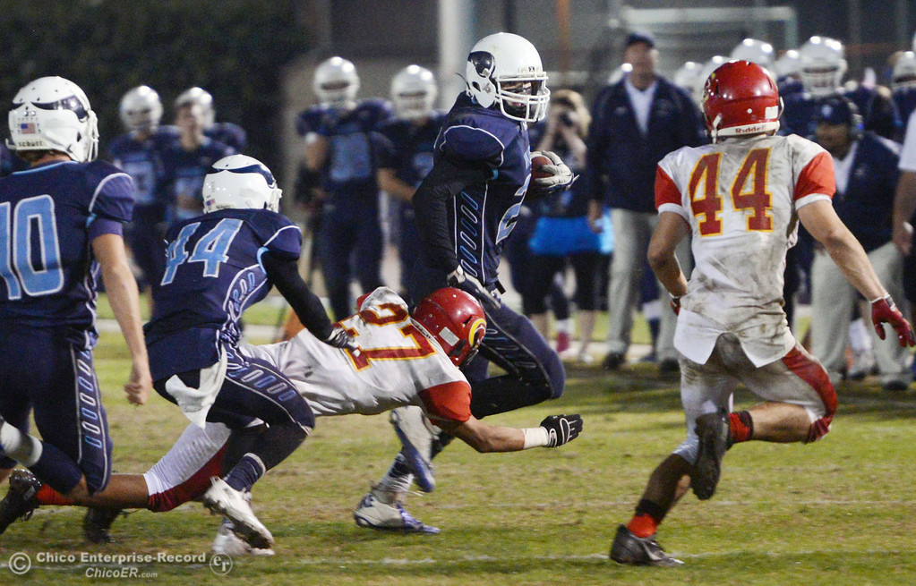 . Pleasant Valley High\'s #25 Ryan Steindorf (right) rushes against Chico High\'s #27 Noah Collado (left) in the fourth quarter of their Almond Bowl football game at CSUC University Stadium Friday, November 1, 2013 in Chico, Calif.  (Jason Halley/Chico Enterprise-Record)