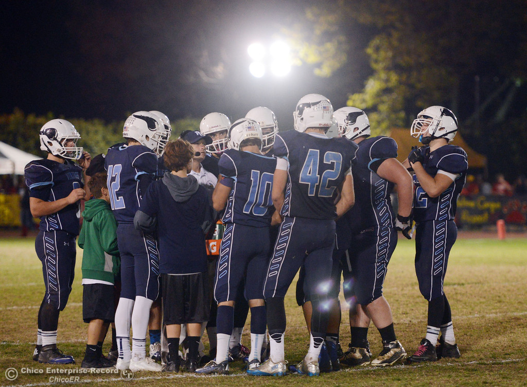 . Pleasant Valley High coach Mark Cooley (center) talks to the team during a timeout against Chico High in the second quarter of their Almond Bowl football game at CSUC University Stadium Friday, November 1, 2013 in Chico, Calif.  (Jason Halley/Chico Enterprise-Record)
