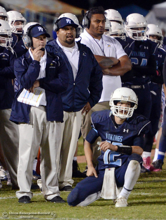 . Pleasant Valley High\'s #12 Trent Darms (right) takes a knee next to coach Mark Cooley in the third quarter of their Almond Bowl football game at CSUC University Stadium Friday, November 1, 2013 in Chico, Calif.  (Jason Halley/Chico Enterprise-Record)