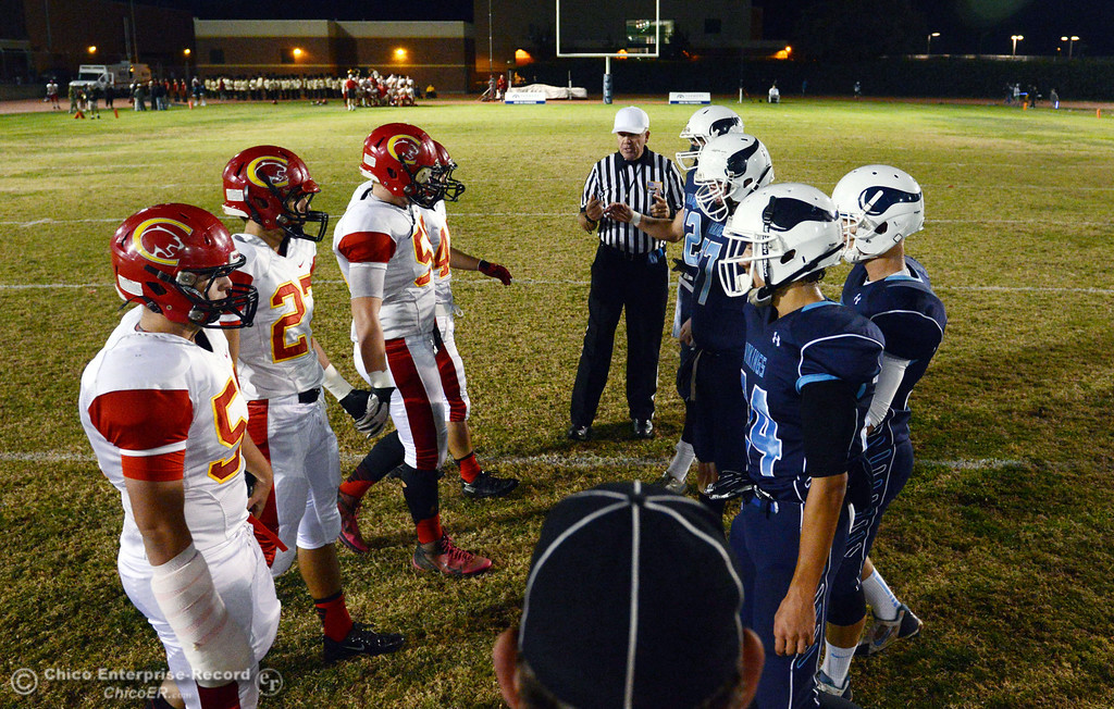 . Chico High\'s #51 Kody Sonday, #27 Noah Collado, #58 Malik Hopkins, and #44 Cyland Leitner come out for the coin toss against Pleasant Valley High\'s #42 Chad Olsen, #77 Tyler Stimac, #35 Benjamin Whitmore, and #24 Jack Soza (left to right) in the first quarter of their Almond Bowl football game at CSUC University Stadium Friday, November 1, 2013 in Chico, Calif.  (Jason Halley/Chico Enterprise-Record)