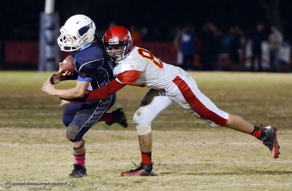 . Pleasant Valley High\'s #28 Dylan Batie (left) is tackled against Chico High\'s #81 Nathan Heyl (right) in the second quarter of their Almond Bowl football game at CSUC University Stadium Friday, November 1, 2013 in Chico, Calif.  (Jason Halley/Chico Enterprise-Record)
