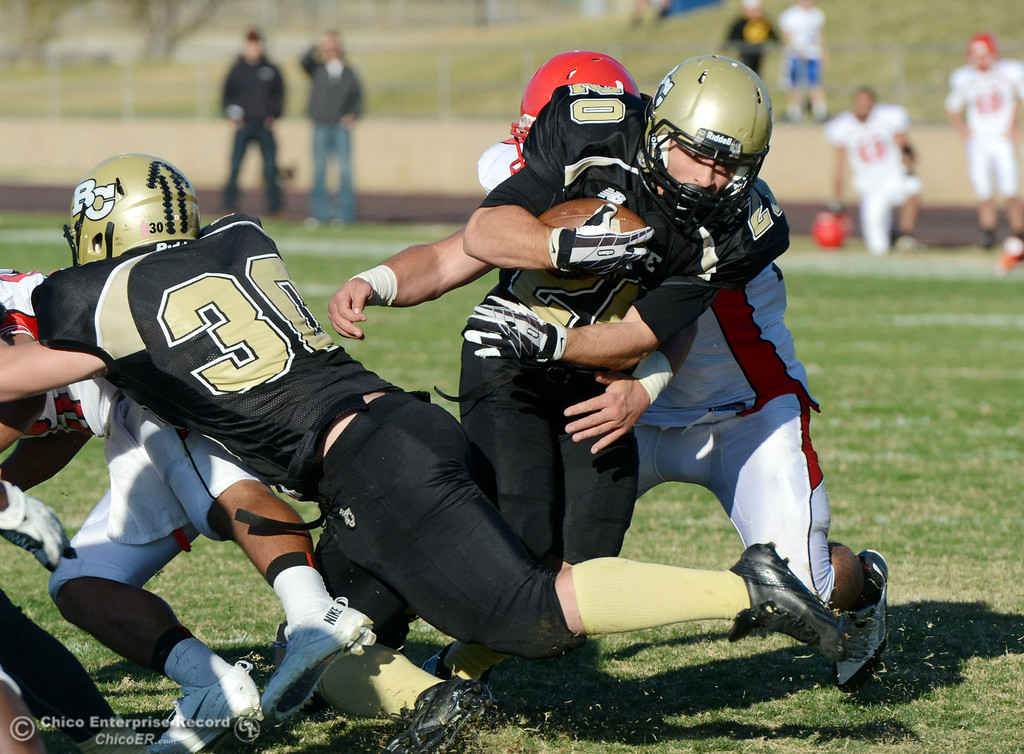 . Butte College\'s #20 Armand Bokitch (center) is tackled against City College of San Francisco\'s #10 Nicholas Holt (back) in the third quarter of their football game at Butte\'s Cowan Stadium Saturday, November 16, 2013 in Butte Valley, Calif.  (Jason Halley/Chico Enterprise-Record)