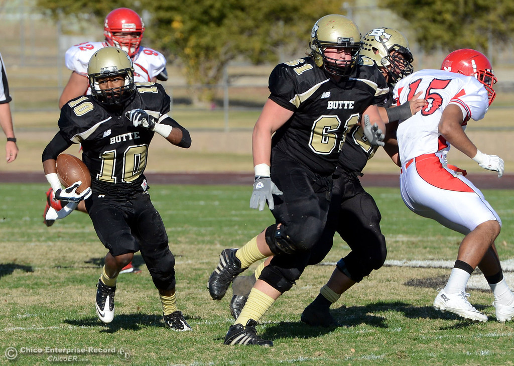 . Butte College\'s #10 CJ Grice (left) rushes against City College of San Francisco in the second quarter of their football game at Butte\'s Cowan Stadium Saturday, November 16, 2013 in Butte Valley, Calif.  (Jason Halley/Chico Enterprise-Record)