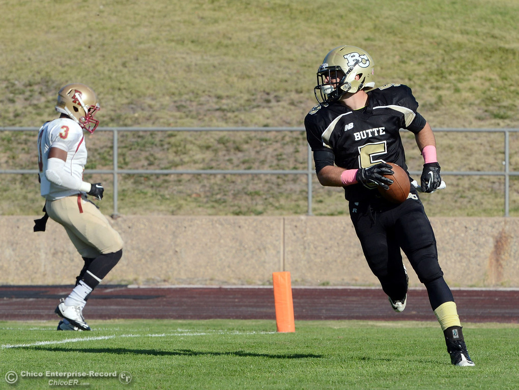 . Butte College\'s #5 David Brannon (right) rushes for a touchdown against De Anza College\'s #3 Johnny Beard (left) in the third quarter of their football game at Butte\'s Cowan Stadium Saturday, October 26, 2013 in Oroville, Calif.  (Jason Halley/Chico Enterprise-Record)