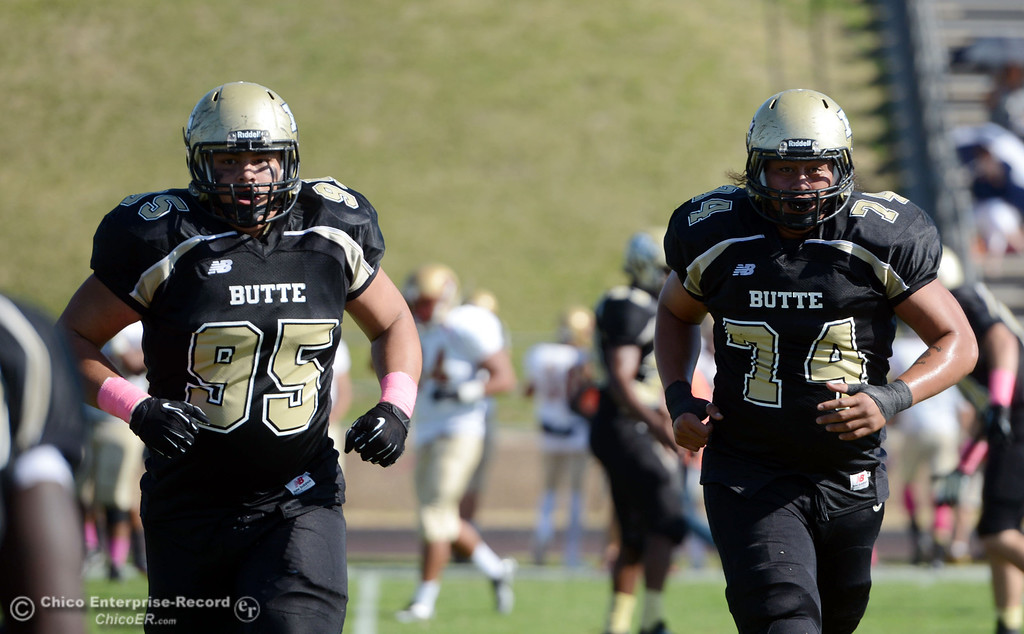. Butte College\'s #95 Mark Rosenquist (left) and #74 Christopher Siliga (right) come off the field against De Anza College in the first quarter of their football game at Butte\'s Cowan Stadium Saturday, October 26, 2013 in Oroville, Calif.  (Jason Halley/Chico Enterprise-Record)