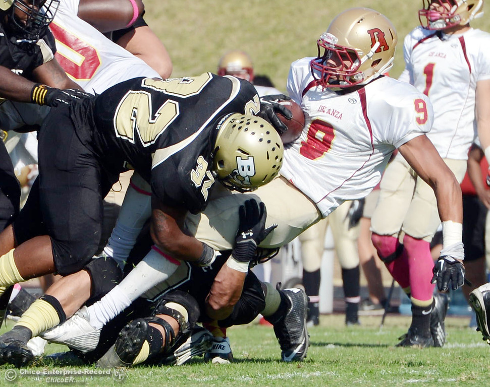 . Butte College\'s #9 Tyler Adair (bottom) and #32 Brian Anderson (left) tackle against De Anza College\'s #9 Justin Arcune (right) in the second quarter of their football game at Butte\'s Cowan Stadium Saturday, October 26, 2013 in Oroville, Calif.  (Jason Halley/Chico Enterprise-Record)