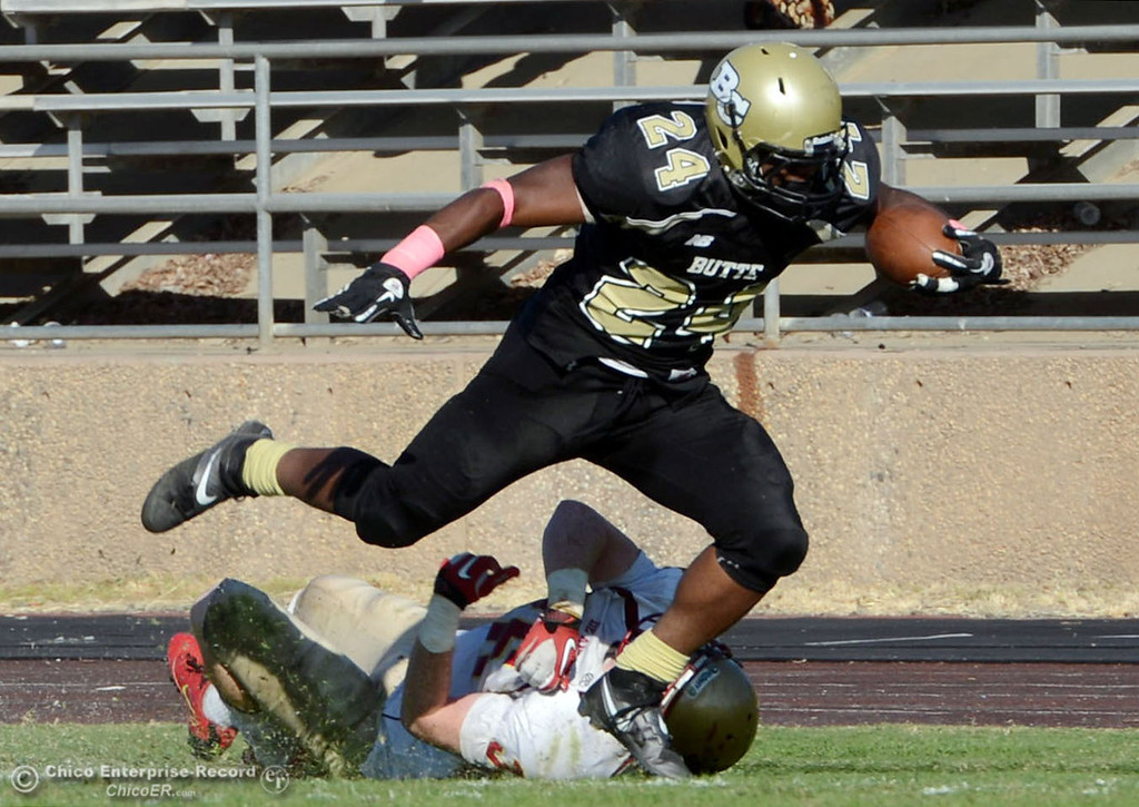 . Butte College\'s #24 Kendall WIlliams (top) is tackled against De Anza College\'s #36 Brandon Martinez (bottom) in the third quarter of their football game at Butte\'s Cowan Stadium Saturday, October 26, 2013 in Oroville, Calif.  (Jason Halley/Chico Enterprise-Record)
