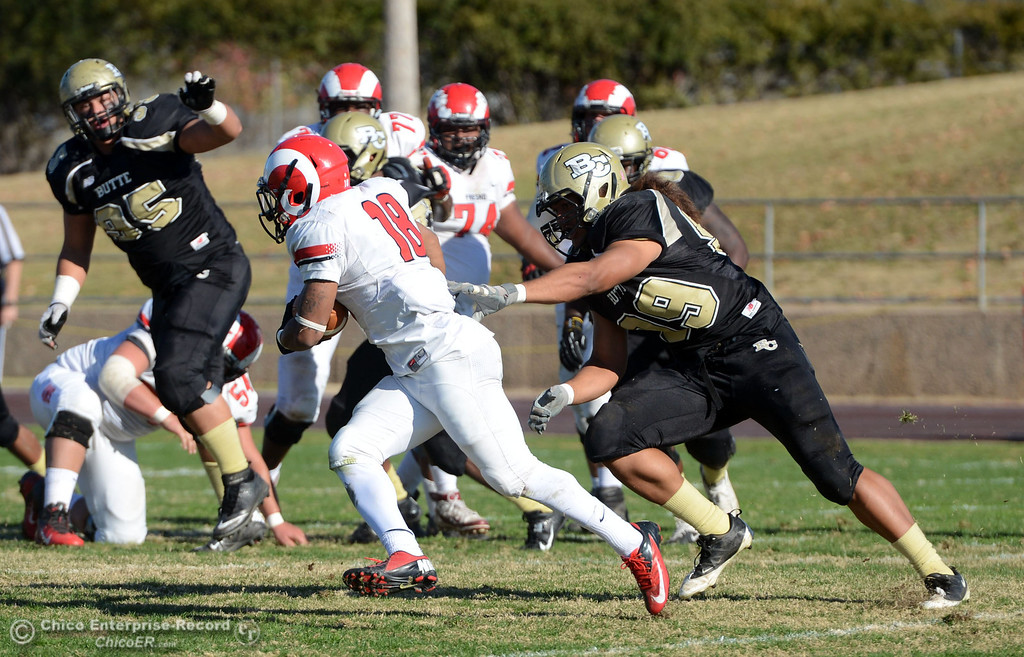 . Butte College\'s #99 Leopeni Siania (right) defends against Fresno City College\'s #18 Micah Ledezma (left) in the second quarter of their football game at Butte\'s Cowan Stadium Saturday, November 30, 2013 in Butte Valley, Calif.  (Jason Halley/Chico Enterprise-Record)