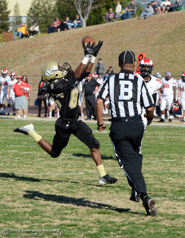 . Butte College\'s #87 Timazray Shepherd (right) scores a touchdown against Fresno City College\'s #21 Garrett Steele (left) in the second quarter of their football game at Butte\'s Cowan Stadium Saturday, November 30, 2013 in Butte Valley, Calif.  (Jason Halley/Chico Enterprise-Record)